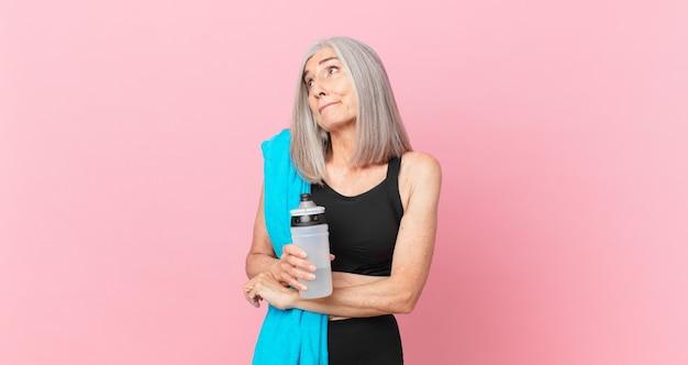 Mulher de meia-idade de cabelos brancos encolhendo os ombros, sentindo-se confusa e incerta com uma toalha e uma garrafa de água. conceito de fitness