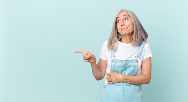 Mulher de meia-idade de cabelos brancos encolhendo os ombros, sentindo-se confusa e incerta e apontando para o lado