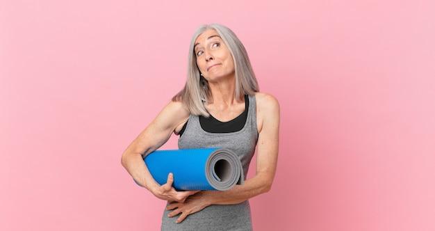 Mulher de meia-idade de cabelos brancos encolhendo os ombros, sentindo-se confusa e incerta e segurando um tapete de ioga. conceito de fitness