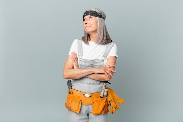 Mulher de meia-idade de cabelos brancos encolhendo os ombros, sentindo-se confusa e incerta e usando roupas de trabalho e ferramentas. conceito de limpeza