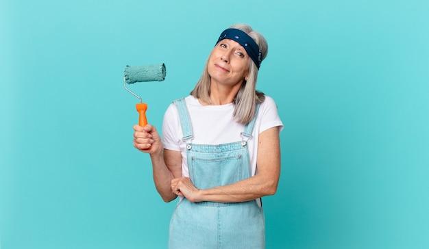 Mulher de meia-idade de cabelos brancos encolhendo os ombros, sentindo-se confusa e insegura com um rolo pintando uma parede