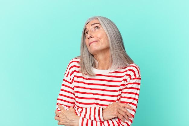 Mulher de meia-idade de cabelos brancos encolhendo os ombros, sentindo-se confusa e insegura