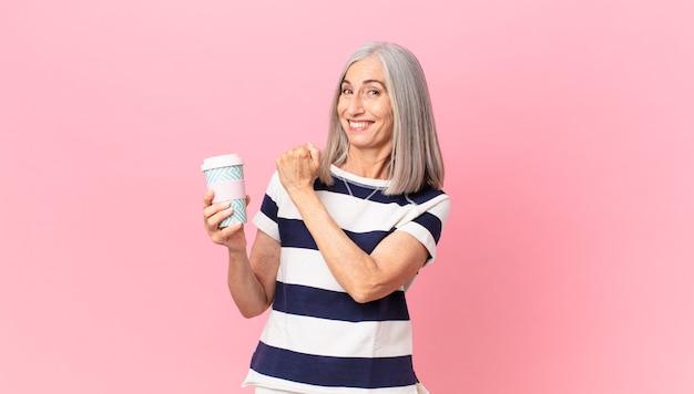 Mulher de meia-idade de cabelos brancos se sentindo feliz e enfrentando um desafio ou comemorando segurando uma vasilha de café para viagem