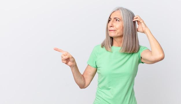 Mulher de meia-idade de cabelos brancos se sentindo perplexa e confusa, coçando a cabeça e apontando para o lado