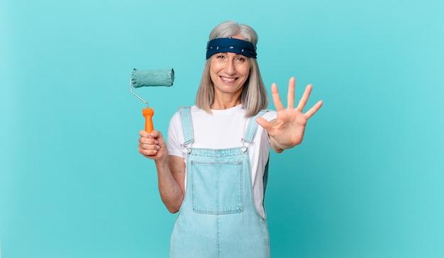 Mulher de meia-idade de cabelos brancos sorrindo e parecendo amigável, mostrando o número cinco com um rolo pintando uma parede