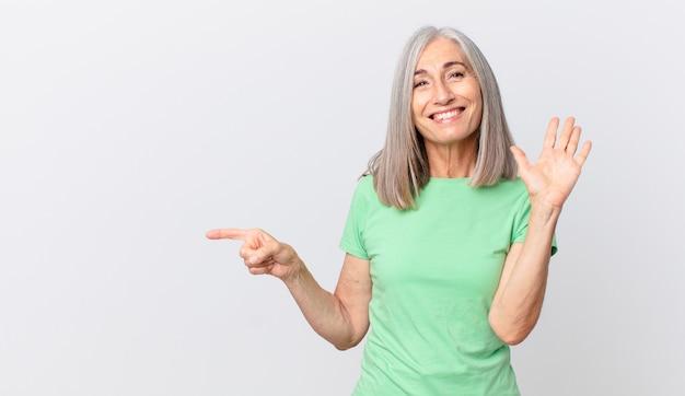 Mulher de meia-idade de cabelos brancos sorrindo feliz, acenando com a mão, dando as boas-vindas, cumprimentando você e apontando para o lado