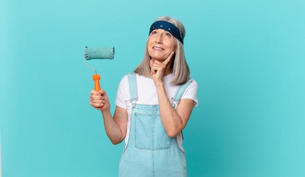 Mulher de meia-idade de cabelos brancos sorrindo feliz e sonhando acordada ou duvidando com um rolo pintando uma parede