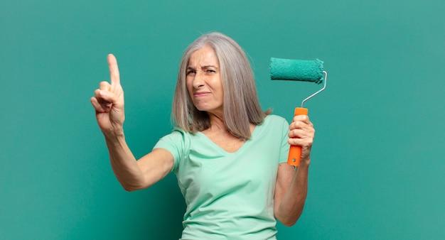 Mulher de meia-idade de cabelos grisalhos com um rolo de pintura decorando a parede