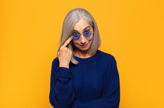 Mulher de meia-idade de olho em você, sem confiança, observando e ficando alerta e vigilante