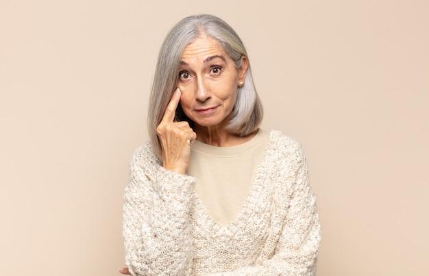 Mulher de meia-idade de olho em você, sem confiar, observando e ficando alerta e vigilante