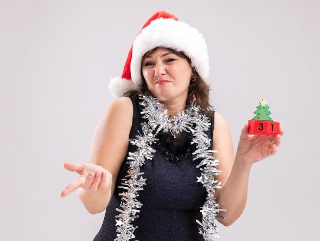 Mulher de meia-idade descontente com chapéu de papai noel e guirlanda de ouropel no pescoço segurando um brinquedo de árvore de natal com data olhando e apontando para o lado isolado no fundo branco