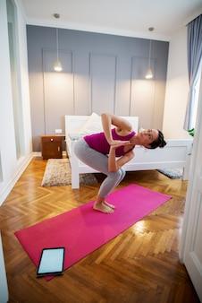 Mulher de meia idade desportiva atraente fazendo exercícios de ioga