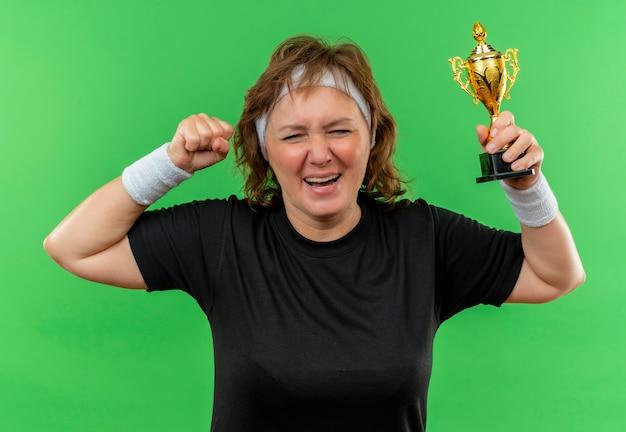 Mulher de meia-idade, desportiva, com uma t-shirt preta e uma faixa a segurar um troféu, cerrando os punhos, feliz e animada, de pé sobre a parede verde