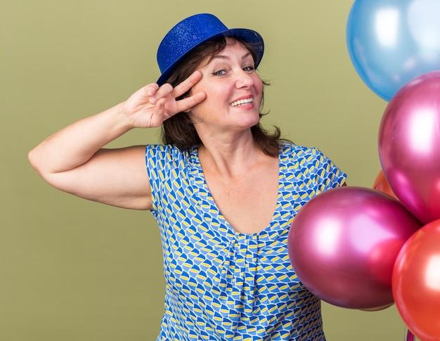 Mulher de meia-idade divertida e alegre com um chapéu de festa com um monte de balões coloridos exibindo o sinal v