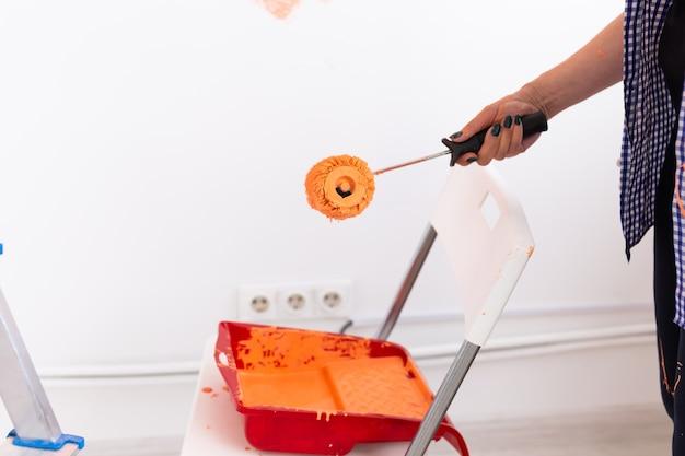 Mulher de meia-idade do close-up pintando a parede interior da casa nova. conceito de redecoração, renovação, reparação e refresco de apartamentos.