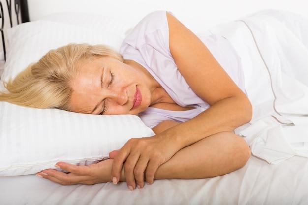 Mulher de meia idade dormindo na cama