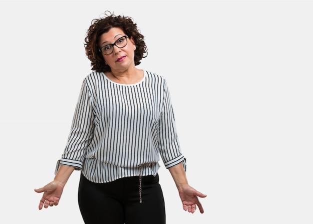 Mulher de meia idade, duvidando e encolhendo os ombros, conceito de indecisão e insegurança, incerta sobre algo