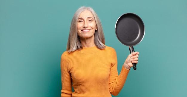 Mulher de meia-idade e cabelos grisalhos, bonita, aprendendo a cozinhar com uma panela