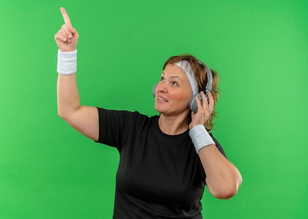 Mulher de meia-idade e esportiva em uma camiseta preta com bandana e fones de ouvido olhando para o lado apontando para cima com o dedo indicador em pé sobre a parede verde