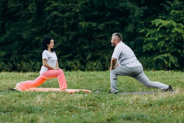 Mulher de meia idade e homem fazendo pose de ioga em pé.