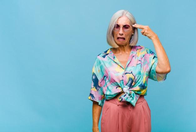 Mulher de meia-idade e legal parecendo infeliz e estressada, gesto suicida fazendo sinal de arma com a mão, apontando para a cabeça
