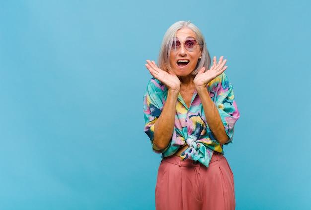 Mulher de meia idade e legal se sentindo chocada e animada, rindo, maravilhada e feliz por causa de uma surpresa inesperada