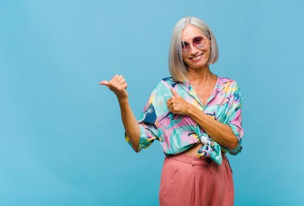 Mulher de meia-idade e legal sorrindo alegre e casualmente apontando para copiar o espaço ao lado, sentindo-se feliz e satisfeita