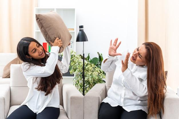 Mulher de meia-idade e sua filha pequena em camisas brancas e calças pretas sentadas nas cadeiras discutindo na sala de estar iluminada