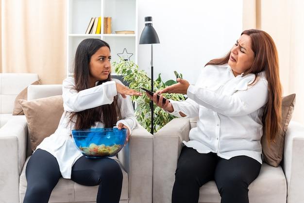 Mulher de meia-idade e sua filha pequena em camisas brancas e calças pretas sentadas nas cadeiras, filha com tigela de batatas fritas, brigando com a mãe na sala de estar iluminada