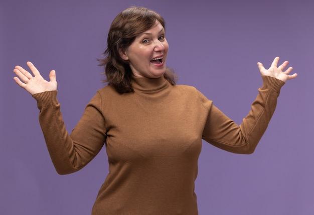 Mulher de meia idade em gola alta marrom feliz e positiva abrindo as mãos em pé sobre a parede roxa