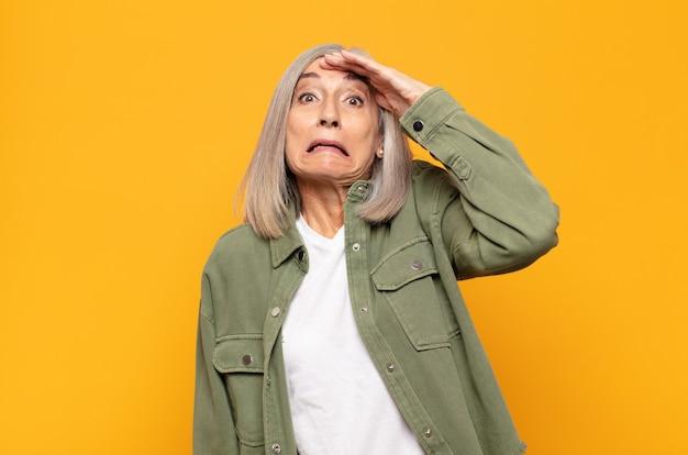 Mulher de meia-idade em pânico por causa de um prazo esquecido, sentindo-se estressada, tendo que cobrir uma bagunça ou erro