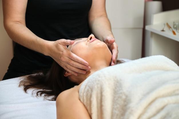 Mulher de meia-idade em salão de beleza spa, deitada na mesa de massagem. feche a massagem no rosto e pescoço. cuidados com o corpo e rosto, saúde, tratamento, cosmetologia, mulheres maduras