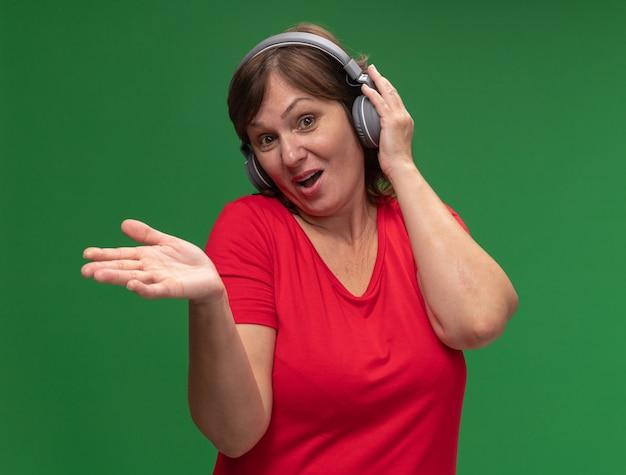 Mulher de meia-idade em uma camiseta vermelha com fones de ouvido confusa, sorrindo, levantando o braço em pé sobre a parede verde