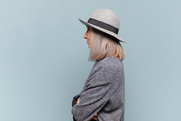 Mulher de meia-idade em vista de perfil olhando para copiar o espaço à frente, pensando, imaginando ou sonhando acordada