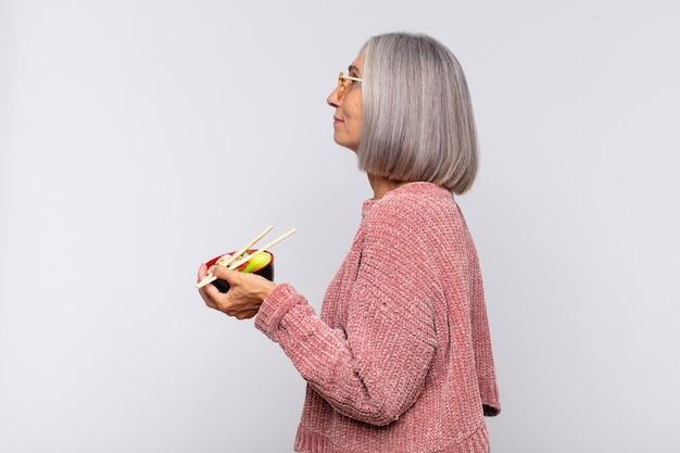 Mulher de meia-idade em vista de perfil, olhando para copiar o espaço à frente, pensando, imaginando ou sonhando com o conceito de comida asiática