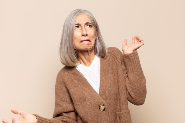 Mulher de meia-idade encolhendo os ombros com uma expressão muda, louca, confusa e perplexa, sentindo-se irritada e sem noção