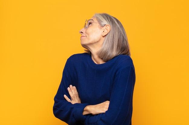 Mulher de meia-idade encolhendo os ombros, sentindo-se confusa e incerta, duvidando com os braços cruzados e olhar perplexo