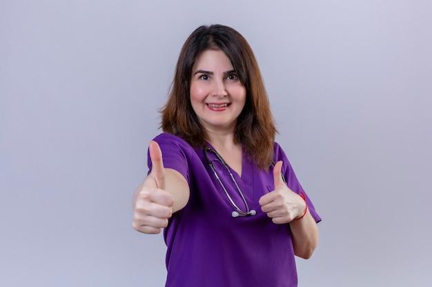 Mulher de meia-idade, enfermeira vestindo uniforme e com estetoscópio olhando para a câmera, saiu feliz e mostrou os polegares em pé sobre um fundo branco