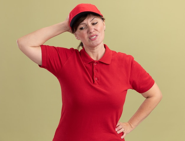 Mulher de meia-idade, entregadora de uniforme vermelho e boné, parecendo confusa com mão na cabeça por engano em pé sobre a parede verde