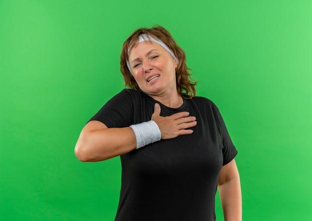 Mulher de meia-idade, esportiva, com camiseta preta e faixa na cabeça, segurando a mão no peito, parecendo indisposta em pé sobre a parede verde