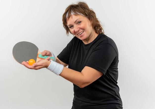 Mulher de meia-idade, esportiva, com camiseta preta e faixa na cabeça, segurando a raquete com bola para tênis de mesa, apontando com um sorriso no rosto feliz em pé sobre a parede branca