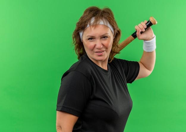 Mulher de meia-idade, esportiva, com camiseta preta e faixa na cabeça, segurando o taco de beisebol, com um sorriso no rosto em pé sobre a parede verde