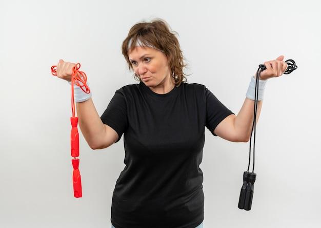 Mulher de meia-idade, esportiva, com camiseta preta e fita na cabeça, segurando duas cordas de pular, parecendo confusa e com dúvidas em pé sobre uma parede branca