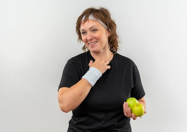 Mulher de meia-idade, esportiva, com camiseta preta e fita na cabeça segurando duas maçãs verdes, sorrindo alegremente em pé sobre uma parede branca