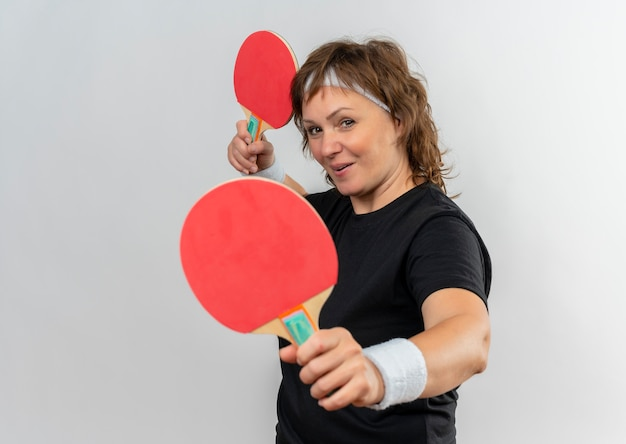 Mulher de meia-idade, esportiva, com camiseta preta e fita na cabeça, segurando duas raquetes de tênis de mesa com um sorriso no rosto em pé sobre uma parede branca