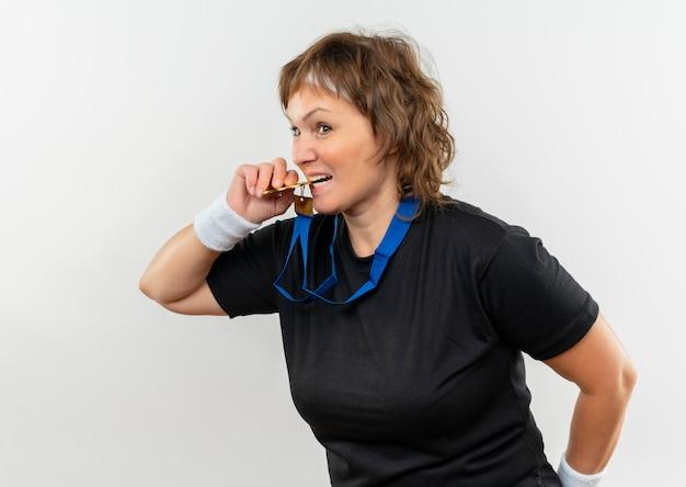 Mulher de meia-idade, esportiva, com camiseta preta, faixa na cabeça e medalha de ouro em volta do pescoço tentando mordê-la em pé sobre uma parede branca