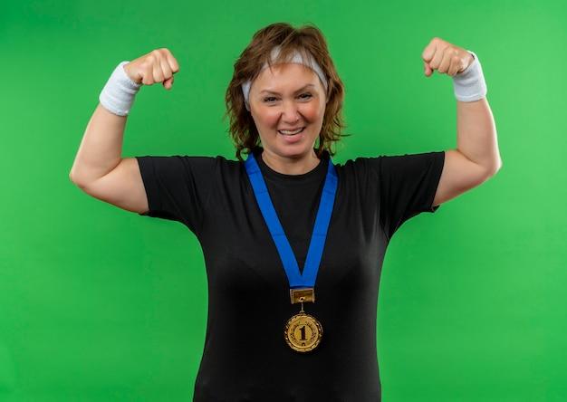 Mulher de meia-idade, esportiva, com camiseta preta, faixa para a cabeça e medalha de ouro em volta do pescoço, cerrando os punhos, feliz e animada em pé sobre a parede verde