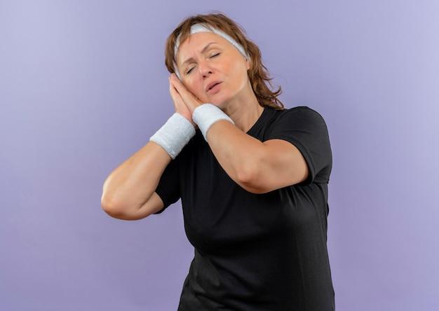Mulher de meia-idade, esportiva, usando uma camiseta preta com uma faixa na cabeça segurando as palmas das mãos juntas, inclinando a cabeça sobre as palmas com os olhos fechados, quer dormir de pé sobre uma parede azul