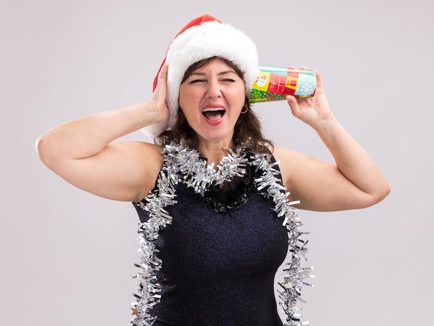 Mulher de meia-idade estressada usando chapéu de papai noel e guirlanda de ouropel no pescoço segurando um copo de plástico de natal próximo à orelha, ouvindo um segredo segurando a mão