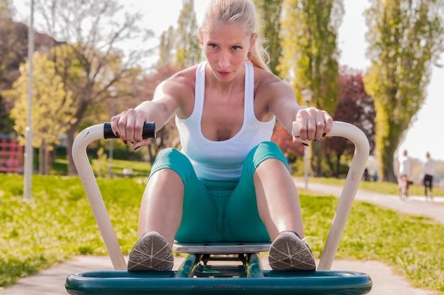 Mulher de meia idade exercitando na máquina de enfileiramento no parque. menina em uma academia do parque. jovem, exercitar, exercício, equipamento, público, parque